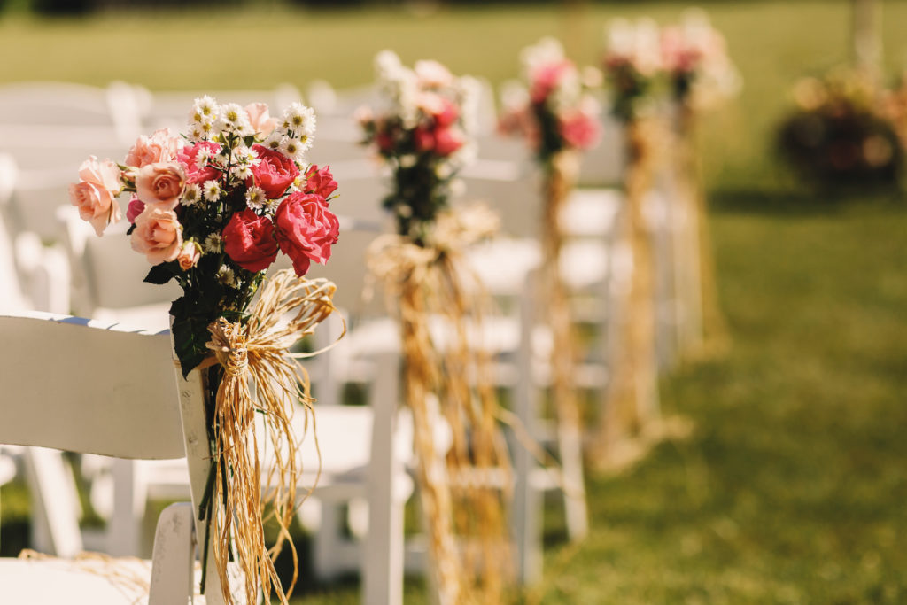 Bows of rope twine pink bouquets to white chairs
